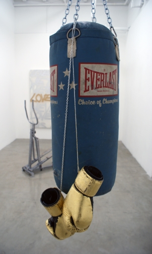 """""""Risk"""" 2011 (Installation materials: punching bag, gold leaf, boxing gloves, embossed stair-stepper, spray-can on canvas.)"""